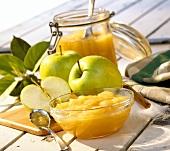 Apfelkompott im Schälchen und Glas; frische grüne Äpfel