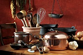 Pans, utensils, vegetables and nuts in rustic kitchen