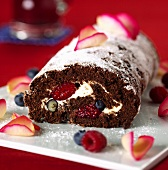 Chocolate roll with berries and icing sugar