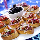 Crostini with toasted cheese and tomatoes; olives