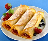 Crepes with berry jam and icing sugar