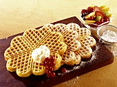 Waffles with icing sugar, cream and fruit