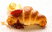 Croissant with butter curl and raspberry jam