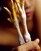 Hand holding chicken's feet