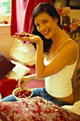 Laughing woman holding bowl of red cherries