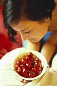 Young woman bending over bowl of red cherries