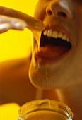 Frau isst Honig mit Finger
