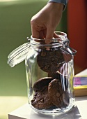 Taking chocolate biscuit out of storage jar