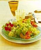 Green salad with soft cheese balls, edible flowers & apricots