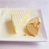 Piece of soft cheese with slices of bread on plate