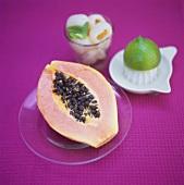 Half a papaya; lychees; lime and lemon squeezer