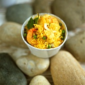Curried rice with fish and shrimps in small bowl