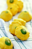 Mini-patty pan squashes on tea towel