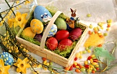 Coloured Easter eggs in chip basket; sugar eggs; spring flowers
