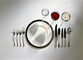 Gedeck für mehrgängiges Menü mit Besteck und Weingläsern