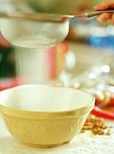 Sieving flour into bowl