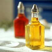 Olive oil and red wine vinegar in small bottles on table