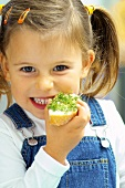 Small girl eating cress and bread