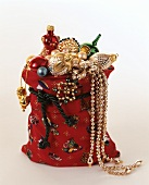 Christmas baubles and gold chains in red sack