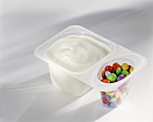 Yoghurt with coloured chocolate beans in pot