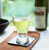 Glass of white wine on small tray in front of wine bottle