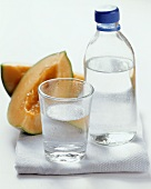 Water in glass and bottle in front of melon slices