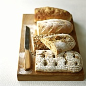 Assorted loaves on wooden chopping board