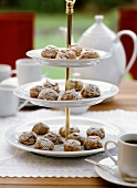 Almond biscuits with icing sugar on tiered stand in open air