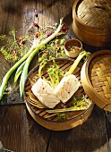 Steamed fish with leeks and dill in bamboo basket