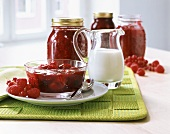 Berry jam in glass bowl and preserving jar; milk jug
