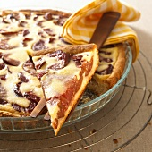 Plum tart, a piece cut, in glass baking dish