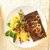 Steak with onions on bread; potato salad