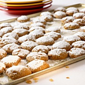 Gingerbread biscuits with icing sugar on baking tray; plate