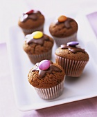Mini-chocolate muffins with  chocolate beans in paper cases