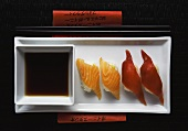 Nigiri-sushi with salmon and tuna; soy sauce