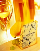 Piece of blue cheese with fruit and glass of white wine