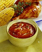 Barbecue sauce; barbecued chicken legs and corncobs