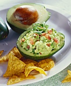 Guacamole in hollowed-out avocado; tortilla chips