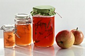 Three jars of apple jelly and two apples