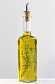 A bottle of olive oil with thyme