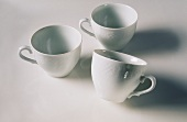Three white coffee cups, one tilted