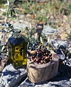 A bottle of olive oil, Nice olives in a wooden bowl