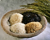 Four different types of rice in a bowl and ears of rice