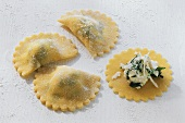 Home-made ravioli with filling on wooden board