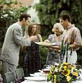 Menschen stehen am festlich gedeckten Tisch im Freien