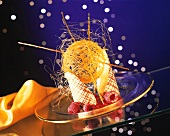 Around the world: curved wafers with a ball of spun caramel and raspberries