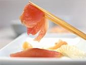 A piece of raw fish on chopsticks (Sashimi sushi)