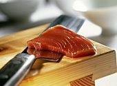 A slice of tuna on a knife (for sushi)