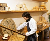 Woman cutting cheese in a cheese shop