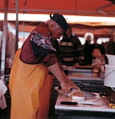 Man slicing salmon; Fish market, Norway